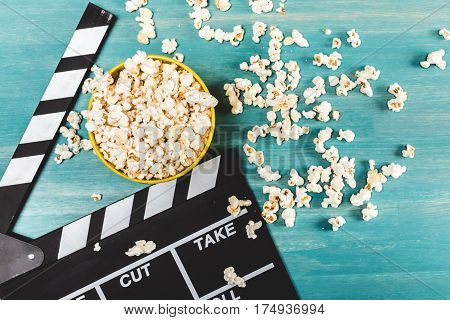 Top view of popcorn and movie clapper on wooden table Movie time concept