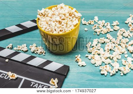 Close-up view of popcorn and movie clapper on wooden table Movie time concept