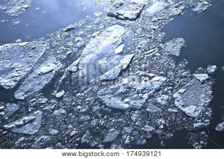 Texture of cracked ice in the blue water .