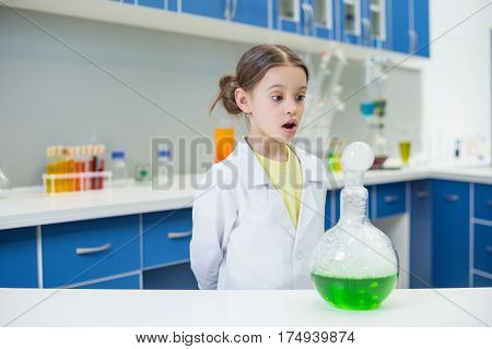 portrait of shocked girl scientist looking at experimental tube in lab