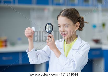 Little girl scientist looking at glass microscope slide through magnifier