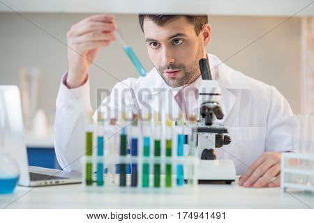 Man scientist in white coat looking at test tube with reagent in lab