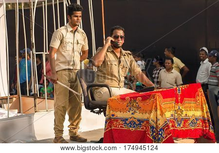 PANAJI, INDIA - FEB 25, 2017: Two indian actors in uniform depict corruption of the police during show of the traditional Goa carnival on February 25, 2017. Carnaval is celebrated in Goa since 18th century