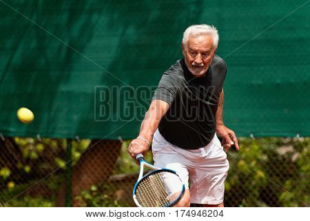 Senior man in action playing tennis, summer time,  color image