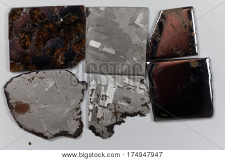 Iron meteorite pieces on a white background.