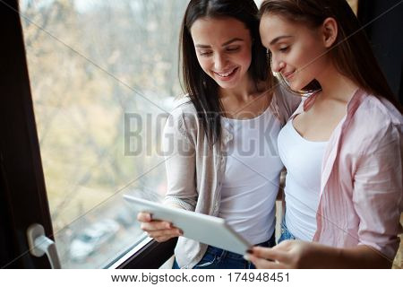 Friendly girls with touchpad spending time in the net