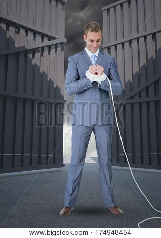 Digital composite image of businessman with hands tied up against opening gates in the background