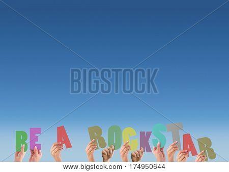 Composite image of hands holding alphabet of be a rockstar against blue background