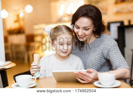 Girl with ice-cream and her mother watching something online in touchpad