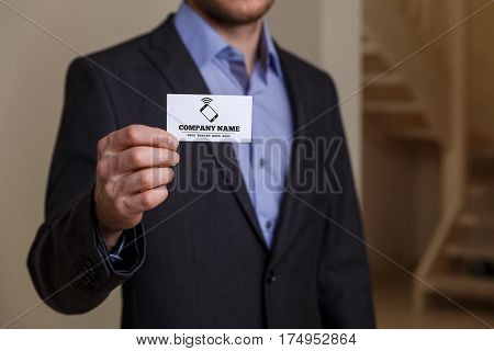 Businessman holding visit card. Man showing blank business card with phone icon. Person in black suit. Mock up design.