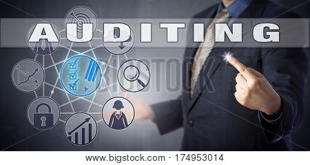 Male corporate accountant in blue business suit activating AUDITING. Business process metaphor and information technology concept for independent examination of accounts assurance and compliance.