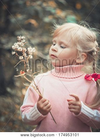 Cute blonde girl blowing dandelion autumn close-up