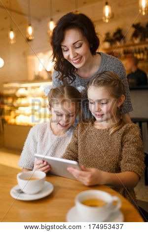 Woman and little girls with touchpad enjoying leisure in cafe