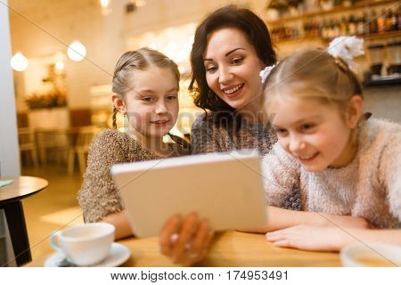 Happy young woman with touchpad showing her twin daughters movie for children