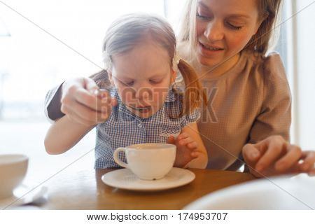 Adorable child sipping hot drink from spoon with her mother near by