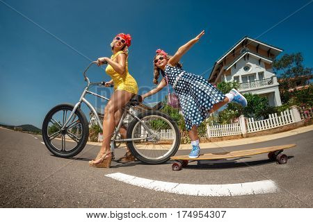 Mother riding bike  with her daughter on skateboard in the suburb street having fun
