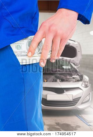 Close-up of mechanic keeping money in his pocket at garage