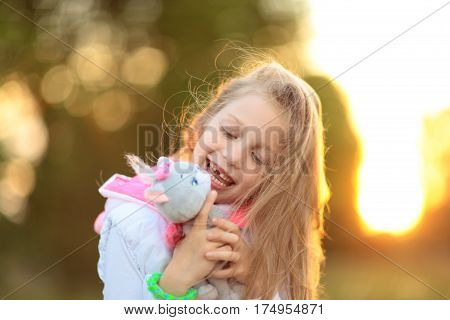 little girl hugging a favorite stuffed animal - a cat for a walk in the Park on a Sunny day.the photo has a empty space for your text