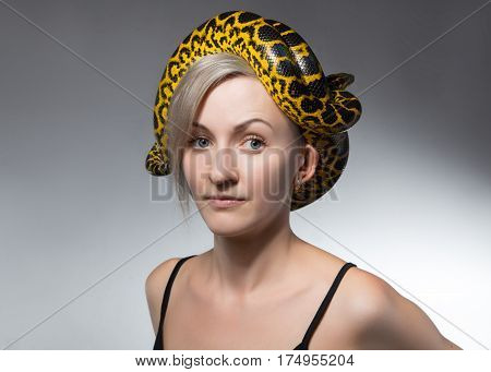 Woman and yellow snake on her head on gray background