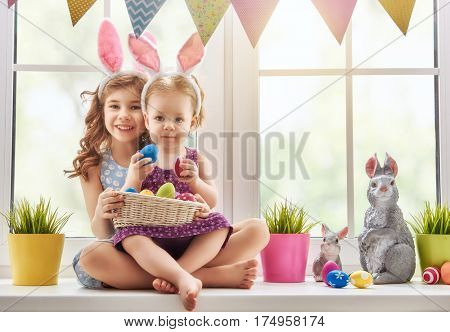 Two cute little children are wearing bunny ears. Girls are sitting on the window with a basket with Easter eggs. Kids laugh and enjoy spring and holiday.