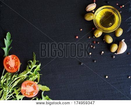 Top View Of Olive Oil And Ingredients - Olives, Garlic And Ruccola On Natural Black Slate Background