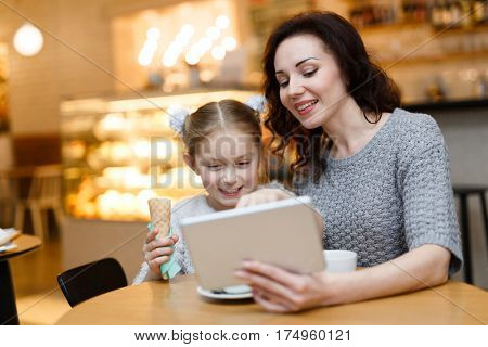 Young woman showing something interesting to her daughter in touchpad