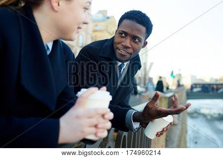 Man and young woman, in street of city, leaning on river bank railing and talking to each other while holding disposable coffee cups both wearing coats