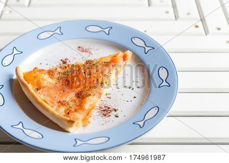 Pizza sliced with smoked salmon and egg on white wooden table