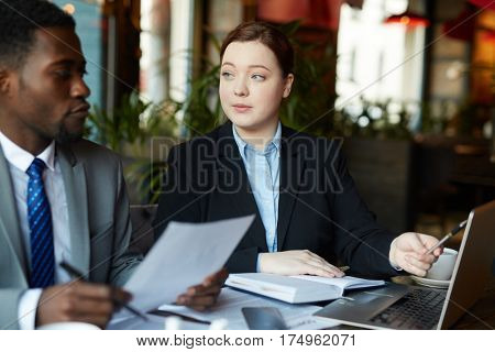 Two business people meeting in modern cafe: Young professional woman pointing at laptop screen while explaining work to African-American partner