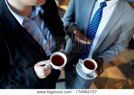 High angle of two business people interacting during coffee break: Unrecognizable businessman talking to colleague gesturing and holding cups with tea