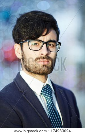 Head and shoulders portrait of young confident Middle-Eastern businessman wearing glasses and elegant suit  looking at camera with serious expression against blurred office background