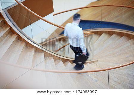 Portrait of unrecognizable blurred businessman going down flight of spiral stairs in modern designer building