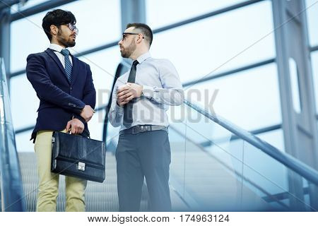 Portrait of two business people talking casually while going down the escalator in modern office building