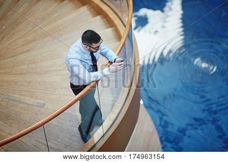 High angle image of modern businessman leaning on railing and typing messages via smartphone in design architectural building