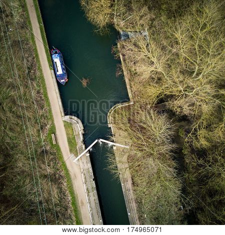 Vertical drone view of an English canal scene with barge lock and towpath surrounded by winter trees on a bright February day.