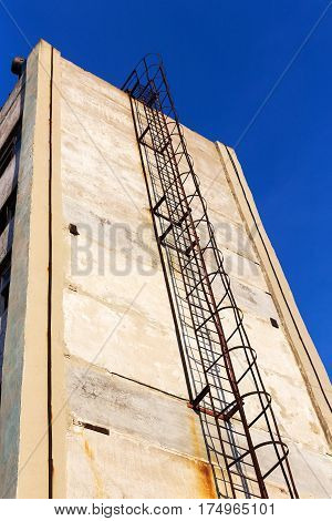 Old Rusty Ply Staircase On The Wall Of The Building Of An Abandoned Factory. The Crisis, The Fall Of