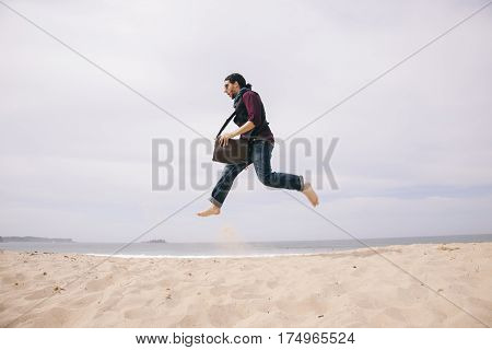 funny young man jumping high on the sand isolated on the beach
