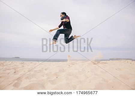 energetic young man jumping high on the sand isolated on the beach