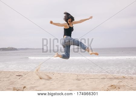 young cheerful woman jumping on the beach on a cloudy day