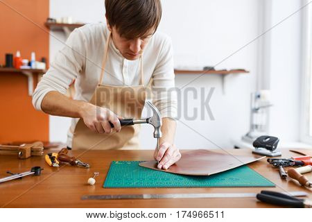 Modern upholsterer with hammer and nail piercing piece of leather