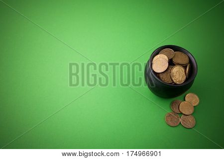 gold coins in a pot on green background