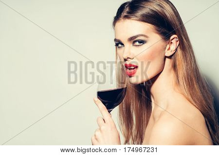 Pretty girl or sexy woman with red lips stylish makeup on beautiful face and long hair drinking wine burgundy color from glass wineglass on grey background copy space