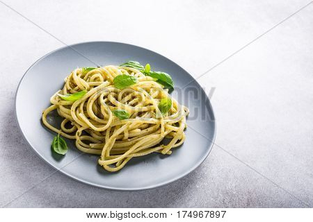 Homemade pasta, spaghetti, linguine with green pesto and basil. Italian healthy food concept with copy space.