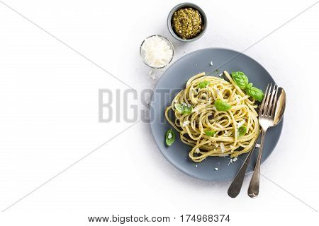 Homemade pasta, spaghetti, linguine with green pesto and basil. Italian healthy food concept with copy space, top view.