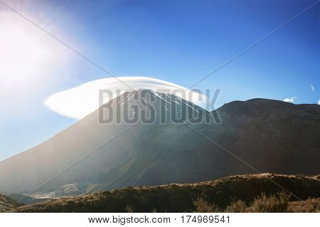 Mount Ngauruhoe with a cloud cap in a morning sun. It is a famous stratovolcano in a Tongariro national park, New Zealand