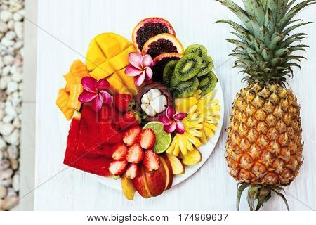 Fresh fruit plate and pineapple, top view from above. Exotic summer diet. Tropical beach lifestyle.