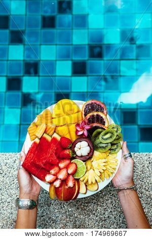 Hands holding served fruit plate above hotel pool. Exotic summer diet. Tropical beach lifestyle.
