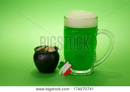 St Patrick's Day green beer with shamrock, horseshoe, pot with coins on green background.