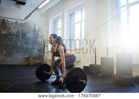 Strong young woman practicing weightlifting