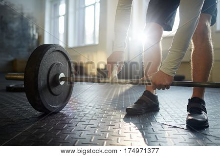 Sportsman rubbing crossbar of barbell with chalk